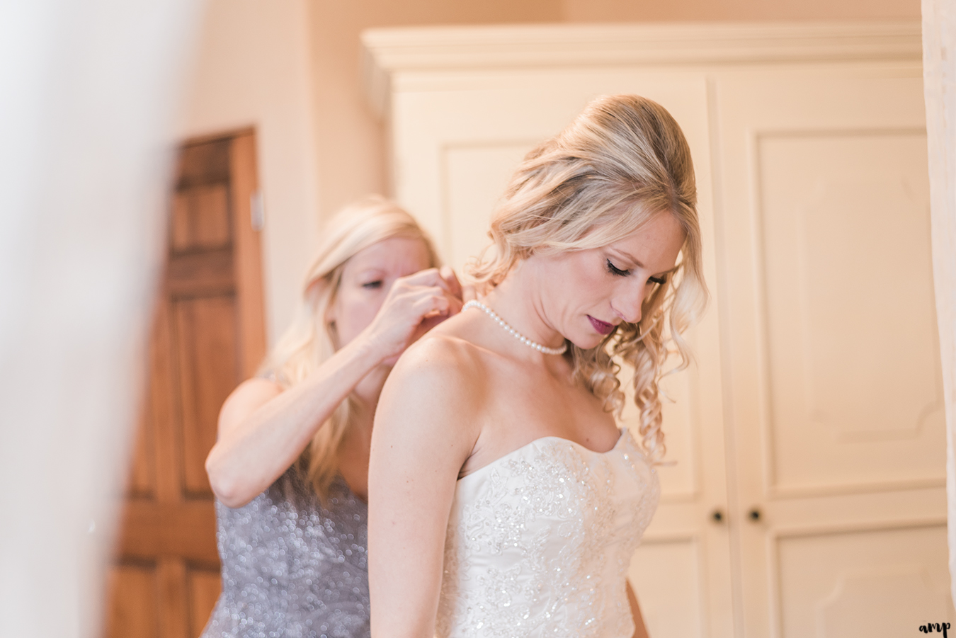 Bride's mom helps her put on her pearl necklace