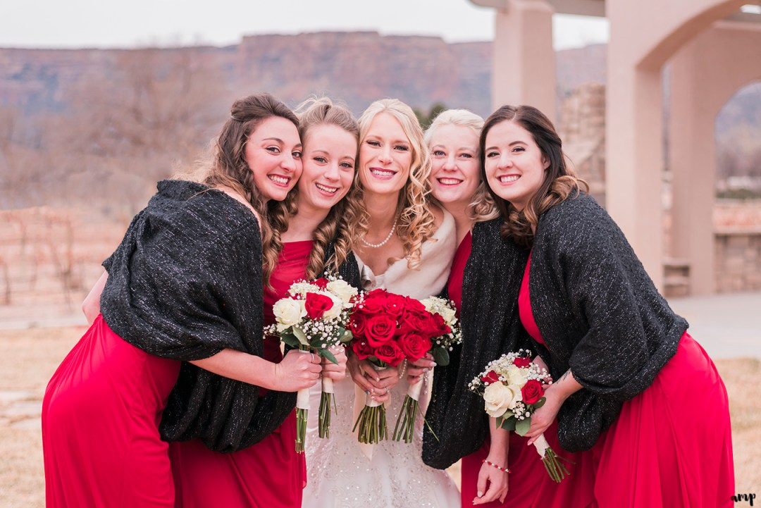 Bridesmaids pose with red roses for her Winter Wedding at Two Rivers Winery in Grand Junction | amanda.matilda.photography