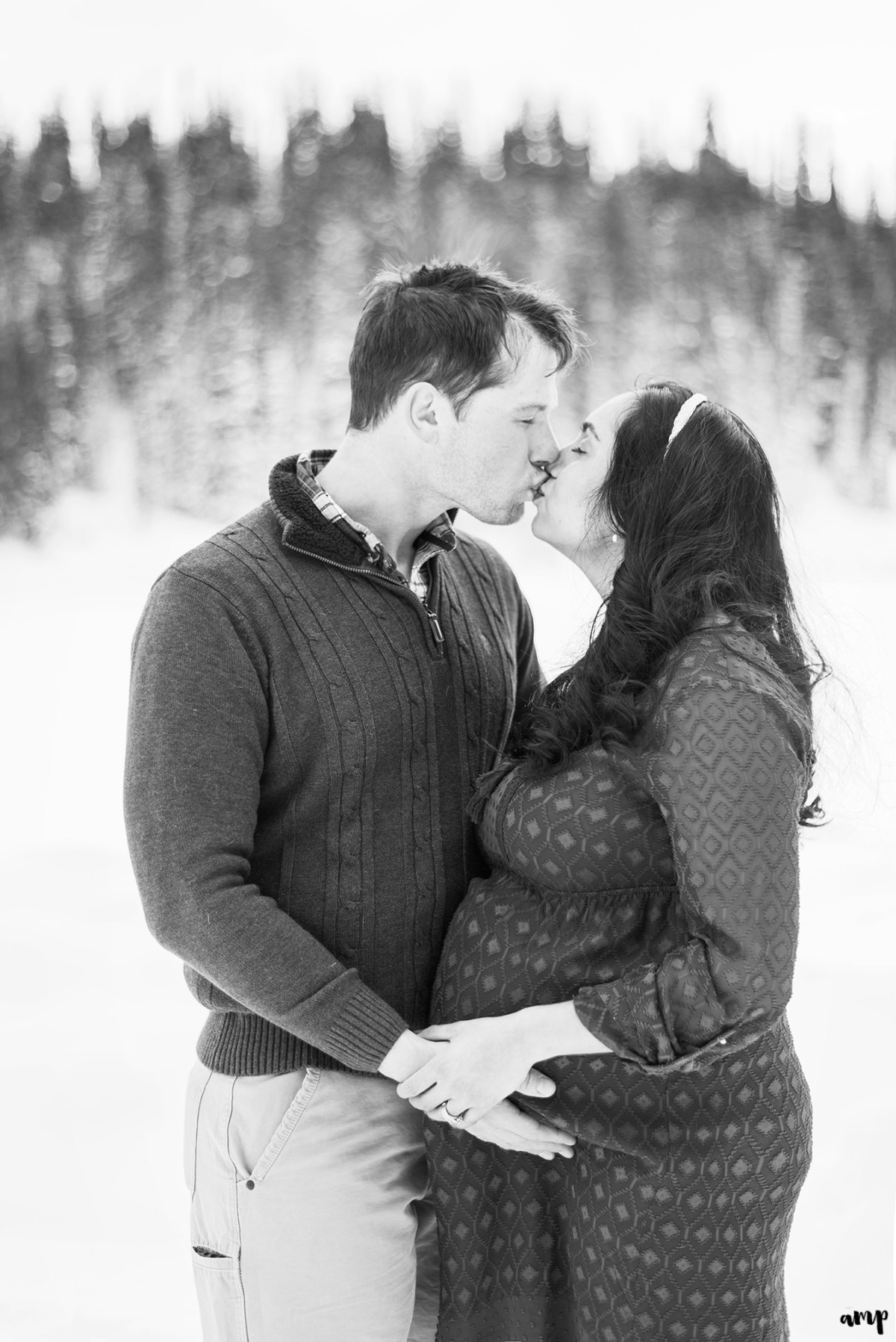 Black and white photo of expecting couple kissing at Mesa Lakes