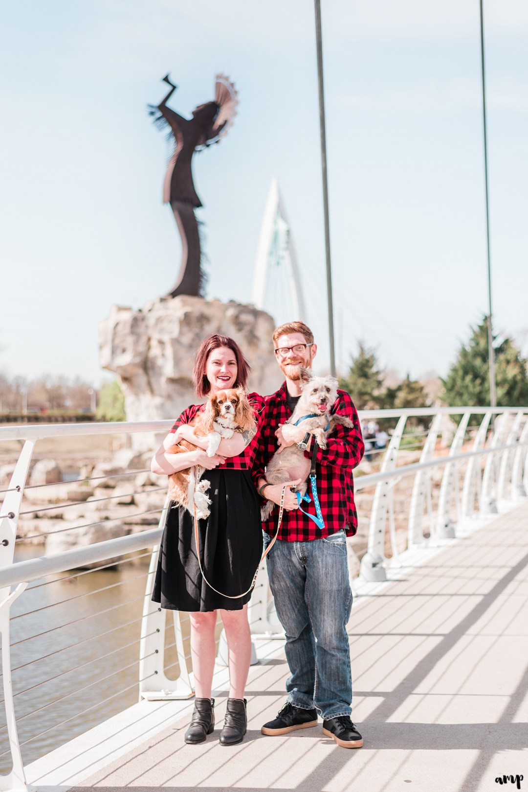 Ben and Courtnee holding their dogs in front of the Keeper of the Plains