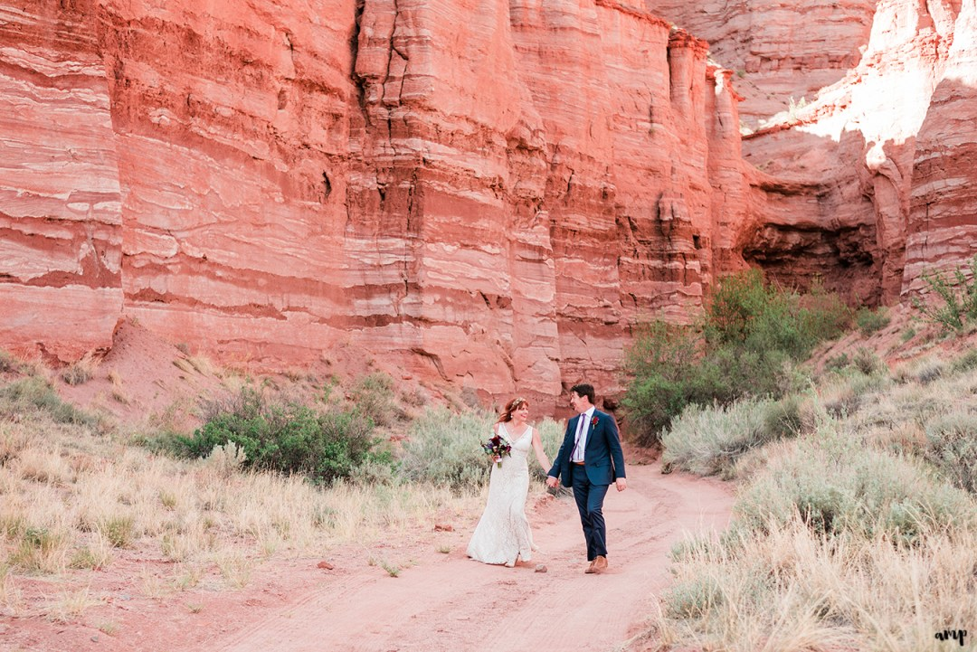 Blake and Carrie walk hand-in-hand under the Palisade of Gateway Canyons