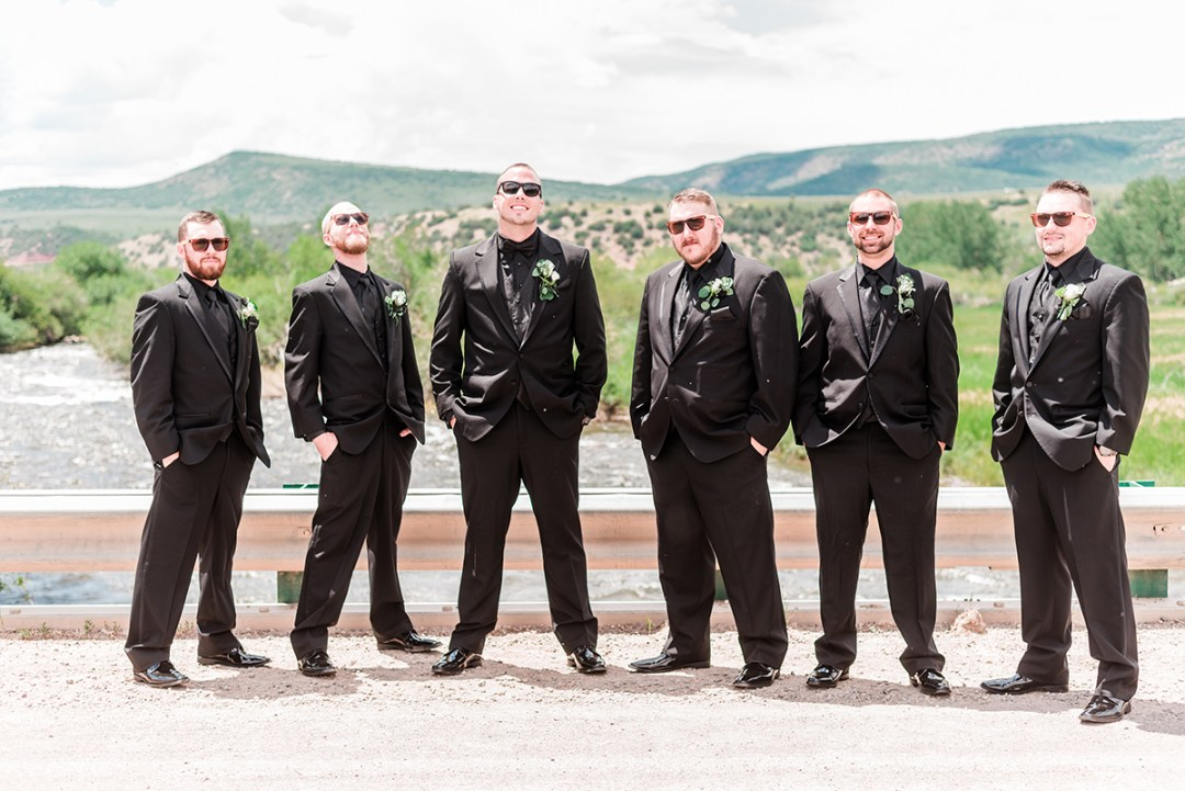 The groomsmen on a bridge with river and mountains in the background