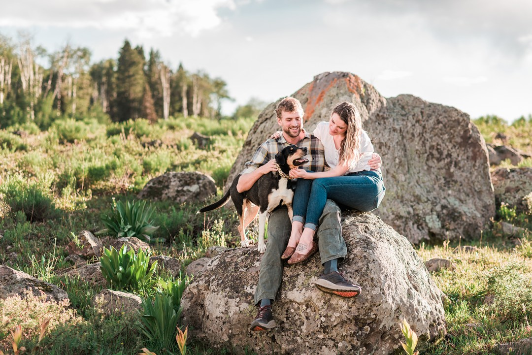 Annie & Taylor sit on a boulder with their dog for their Glenwood Springs Engagement Photos