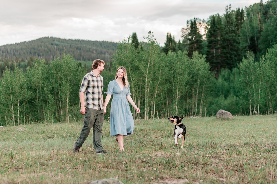 Annie & Taylor walking through a field of wildflowers for their Glenwood Springs Engagement Photos