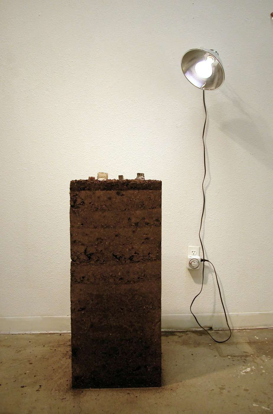 Earth cube, with smaller cubes on top of it, a lamp is on and plugged into the wall.