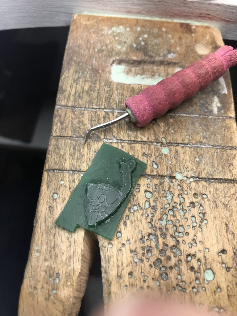 wax carving of a charm in process, with carving tool.