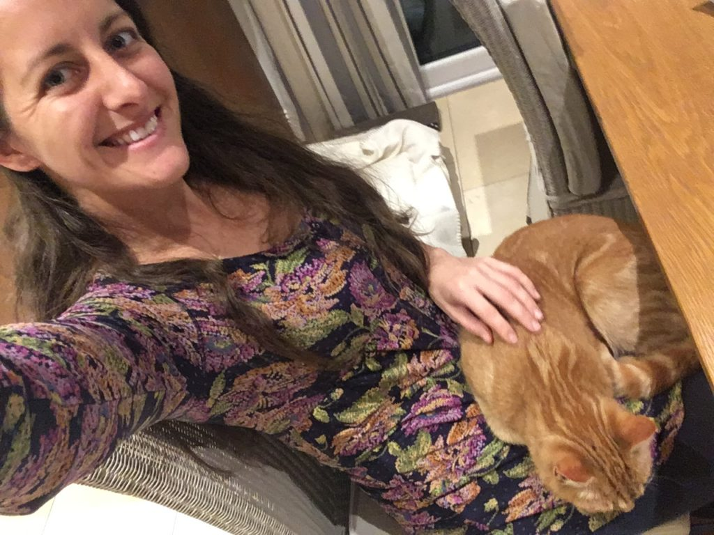 Amanda Walkins, freelance writer and housesitter for TrustedHousesitters, a woman petting an orange cat on her lap
