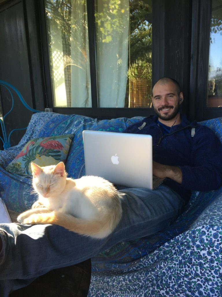 Jonathan Clarkin working on a laptop with Mally the cat sleeping on his legs while housesitting in Spain