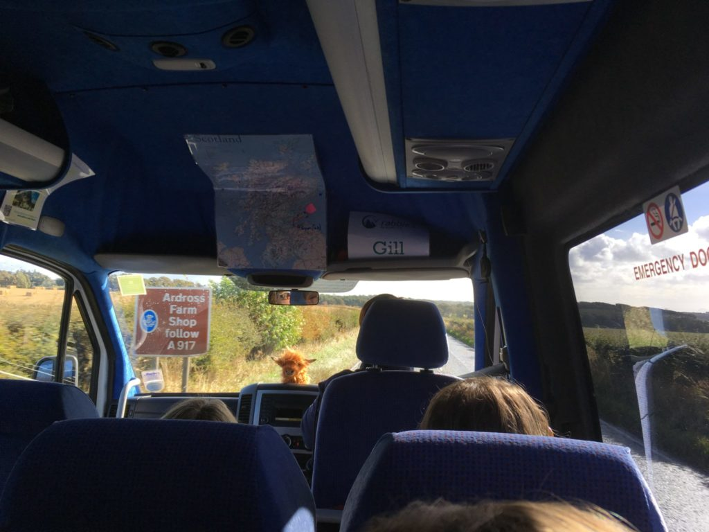 Rabbie's tour bus in Scotland with driver guide Gill at the wheel and Kevin the Coo on the dashboard