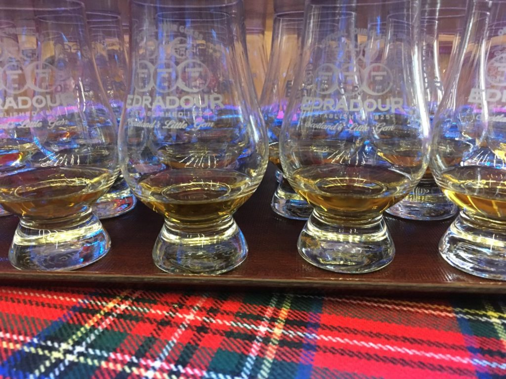 Edradour whisky drams lined up on a tartan blanket