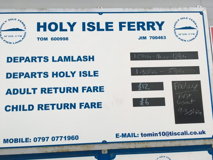 Sign for the Holy Isle ferry in Arran Scotland detailing departure times and costs