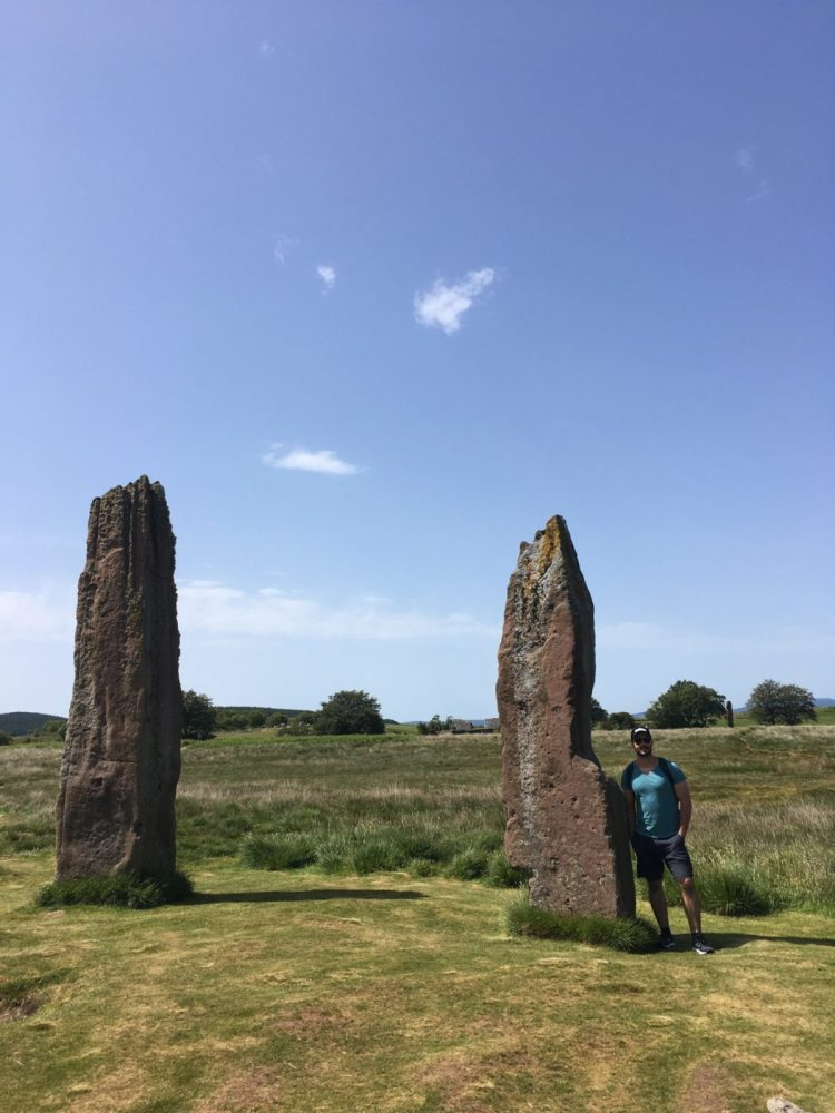 Jonathan Clarkin standing next to a standing stone at Machrie while visiting the Isle of Arran