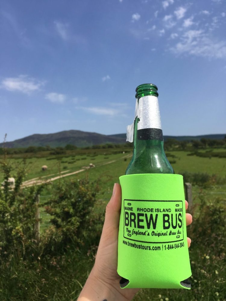 Maine Brew Bus coozie on a beer bottle held up against a blue sky and green fields on a visit to the Isle of Arran in Scotland