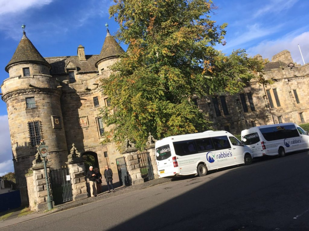 Rabbies tours are perfect day trips from Edinburgh to see more of Scotland - two Rabbies vans are parked in front of Falkland Palace in the sunshine