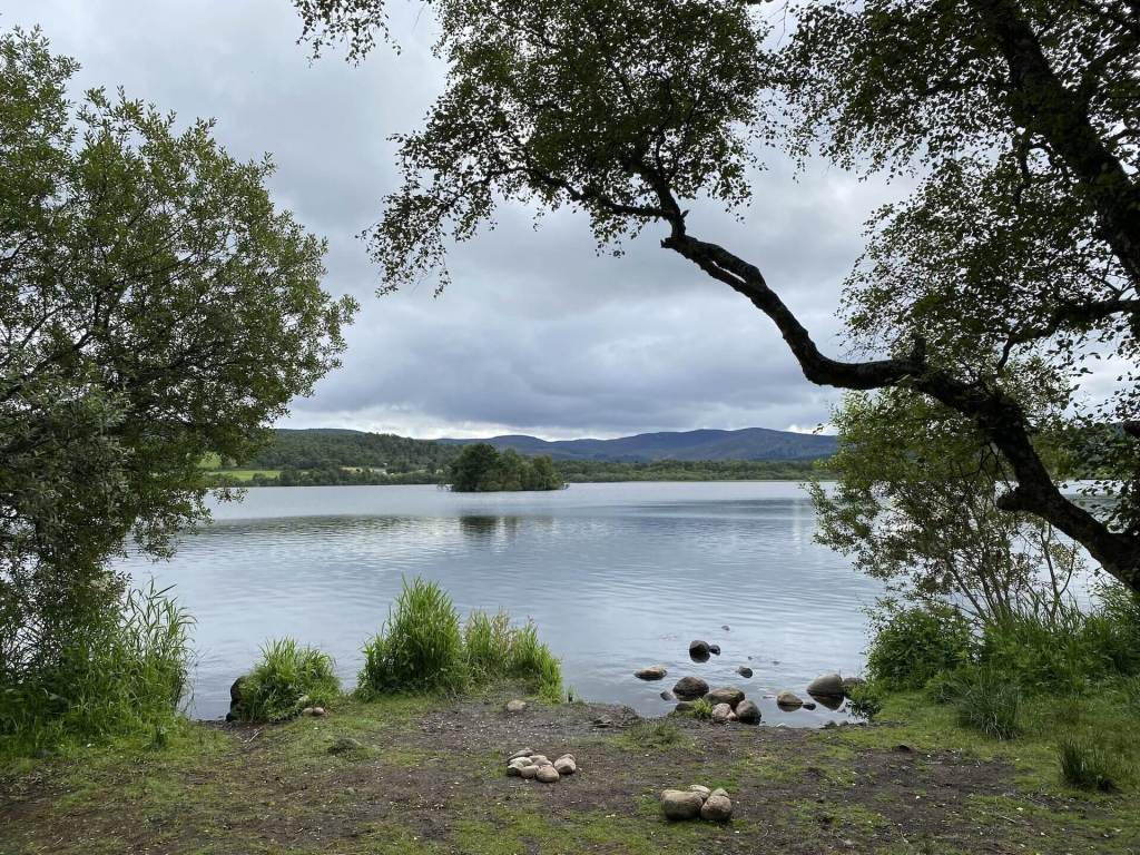 A crannog (a human-made island) rests in Loch Kinord, Muir of Dinnet