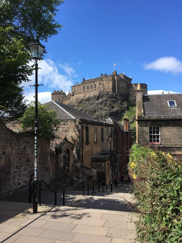 View of Edinburgh Castle from the stairs called The Vennel. A bright blue sky serves as a picture-perfect backdrop