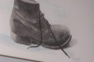 A well worn boot, with the laces undone, the sole showing signs of parting company with the uppers