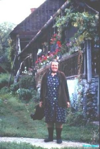 An elderly lady in print dress smiles a greeting in front of her flower decked verandah