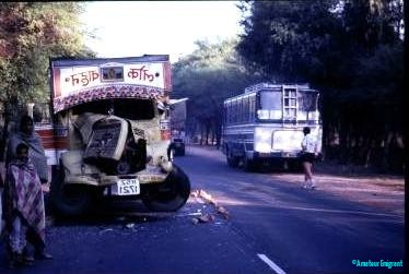 A coach is stationary at the side of the road. On this side of the road is a truck with the bonnet torn off, and the front smashed in by impact with the coach