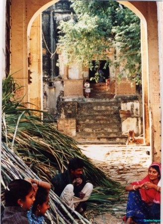 View into a courtyard; sugar cane is piled on one side while the harvesters take a break in the shade