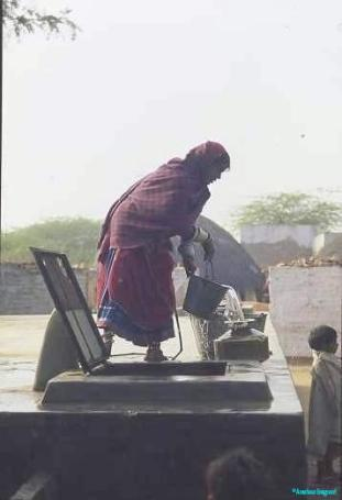 A girl stands atop a concrete tank from which she draws water in a bucket, into a brass water pot to take home.