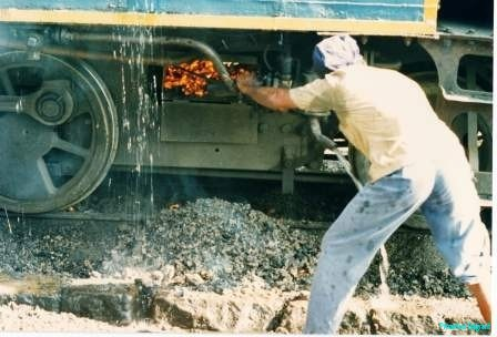 A rail worker bends and rakes out red ashes from beneath a steam train