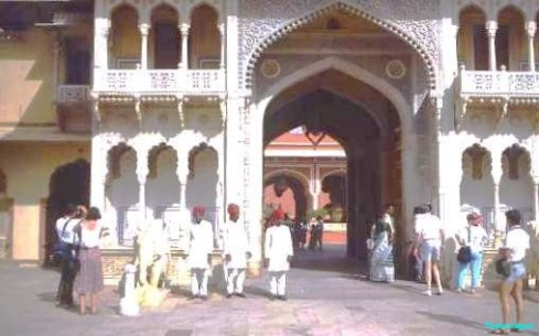A scattering of tourist visitors approach an ornately decorated pointed arch, with other arches lowering the entrance. Balconies with filigreed stonecarving protrude from the main building at the archway sides. Several men in dashing white outfits, topped with scarlet turbans are the 'sentries', very photogenic within the city palace of the maharajah of jaipur in rajasthan