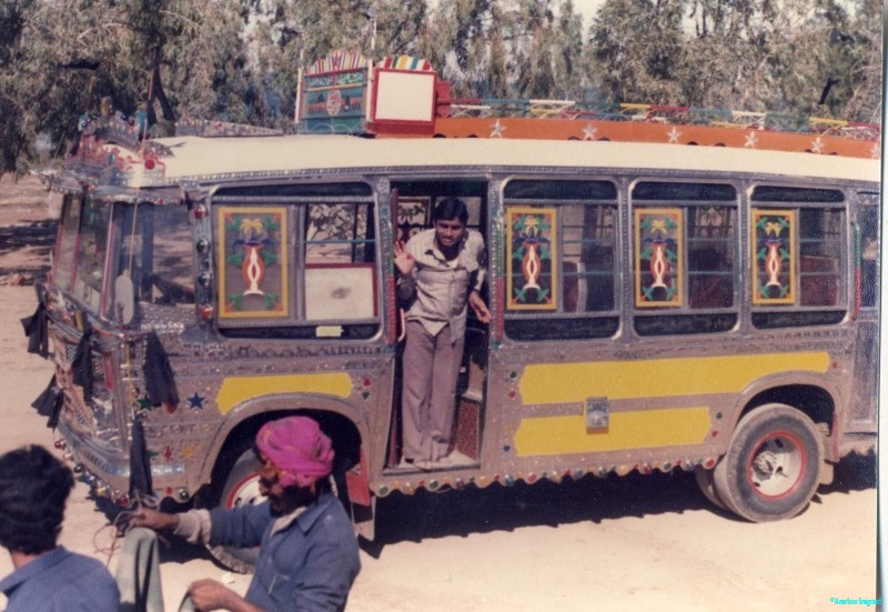 A small bus highly decorated with metal filigree on every edge, multicoloured lights and barred windows
