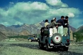 A group of men crowd standing up in the rear of a 4wd pickup, driving along a dirt road into the town. Large snowy mountains form the background in northern Pakistan
