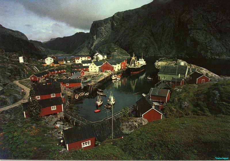 Red and white cabins clustered around a minute sea inlet where a fishing boat is moored