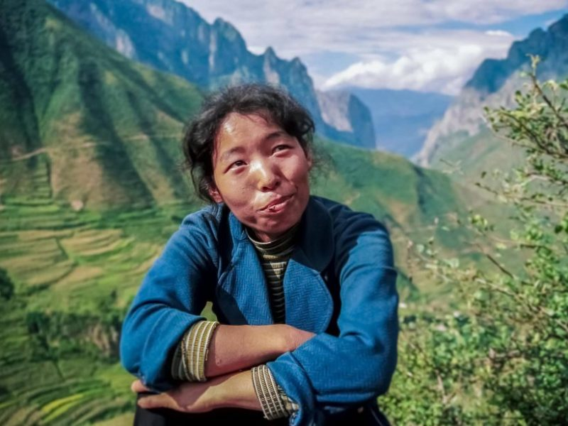 A wry smile for the 'television people' from a woman at the roadside in forested mountains in china