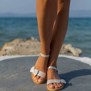 Just what every summer wardrobe needs, the Aphrodite Bow Tie Ivoire Pearl Greek Leather Sandal is every woman's dream pair, super comfy and elegant, and easily combined with any outfit.