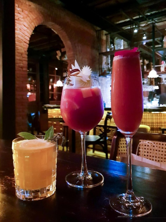3 cocktails set up from the shortest to the tallest. The first one is yellow, the next two various shades of dark pink