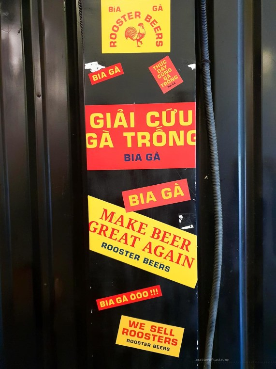 some colourful stickers, mostly in Vietnamese, advertising various Rooster Beers.