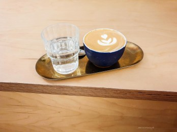 Flat white in a blue cup on a brass -coloured tray with a cup of water next to it.