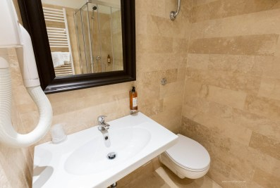 A small part of the bathroom - a white sink, toilet in the corner on the right and a black-framed window above the sink. The towel rack and shower are visible in the reflection.