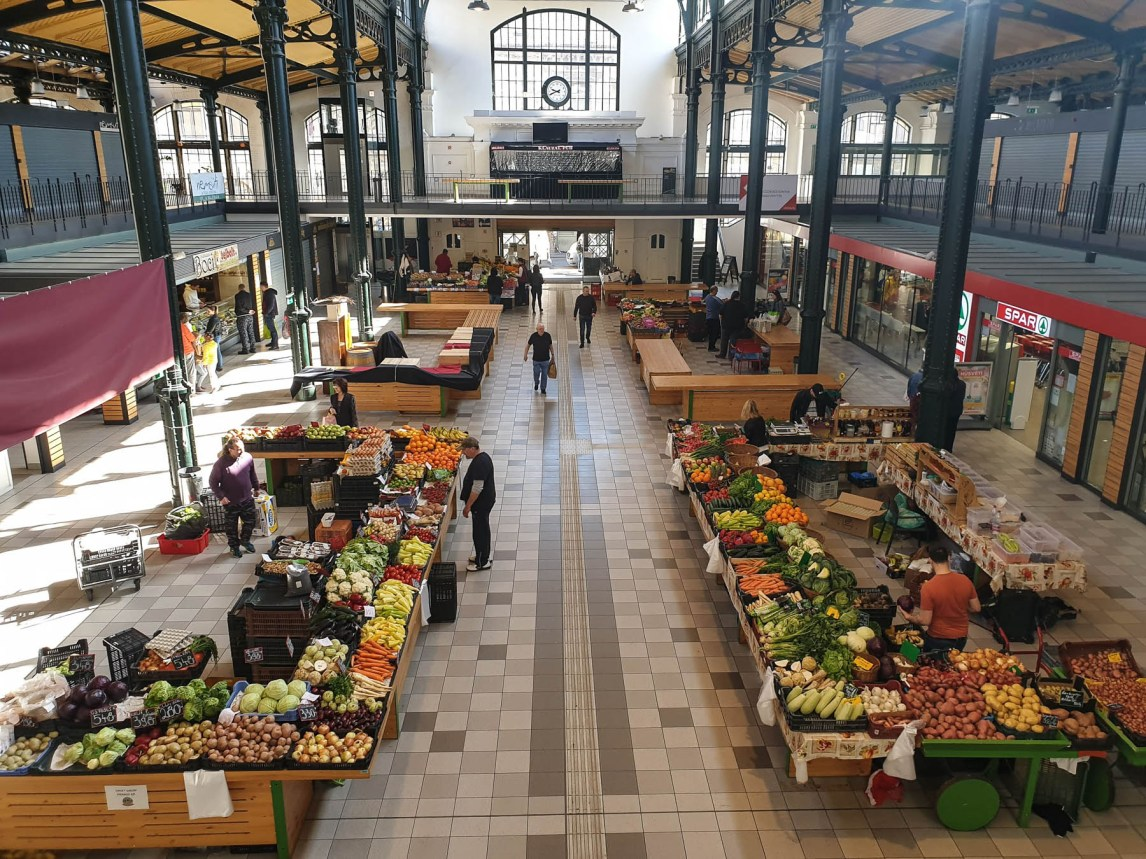 A top view of a small market hall. There are many tables full of colourful vegetables and fruit and a couple of people doing their shopping.