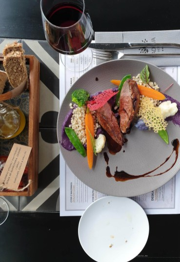 A duck breast dish that looks like a piece of modern art with vibrant colours of vegetables and sauces.