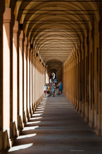 Pastel orange corridor with porticoes on the left side and beautiful arrangement of lights and shadows.