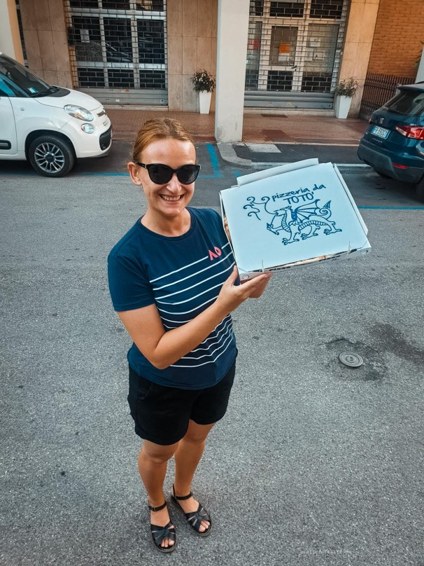 Me standing on a street with a giant box of pizza. I look proud.