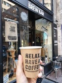 """a paper cup in my hand that reads: relax have a coffee. In the background my favourite coffee shop in Budapest called """"My Little Melbourne Brew Bar""""."""