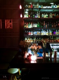 Part of the bar with a bartender working on a cocktail.