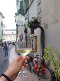 My hand with a glass of local white wine on a small cute street in Trento city centre.