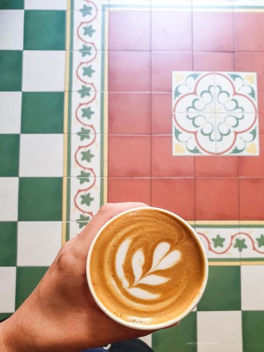 my hand with a cup of beautiful coffee with pretty tiles in the background.
