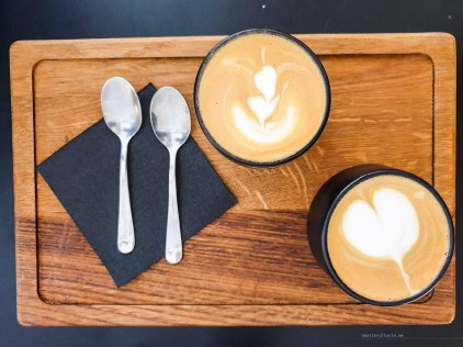 two beautiful flat whites on a wooden board.