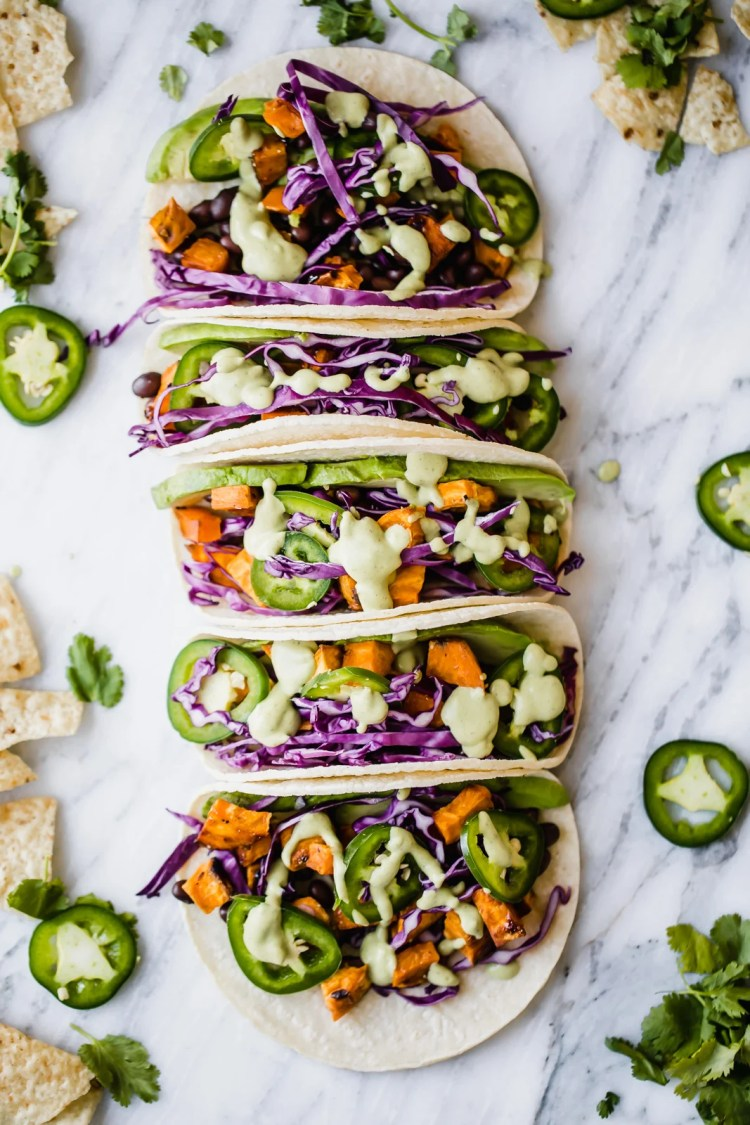 sweet potato black bean tacos in a line on a marble board