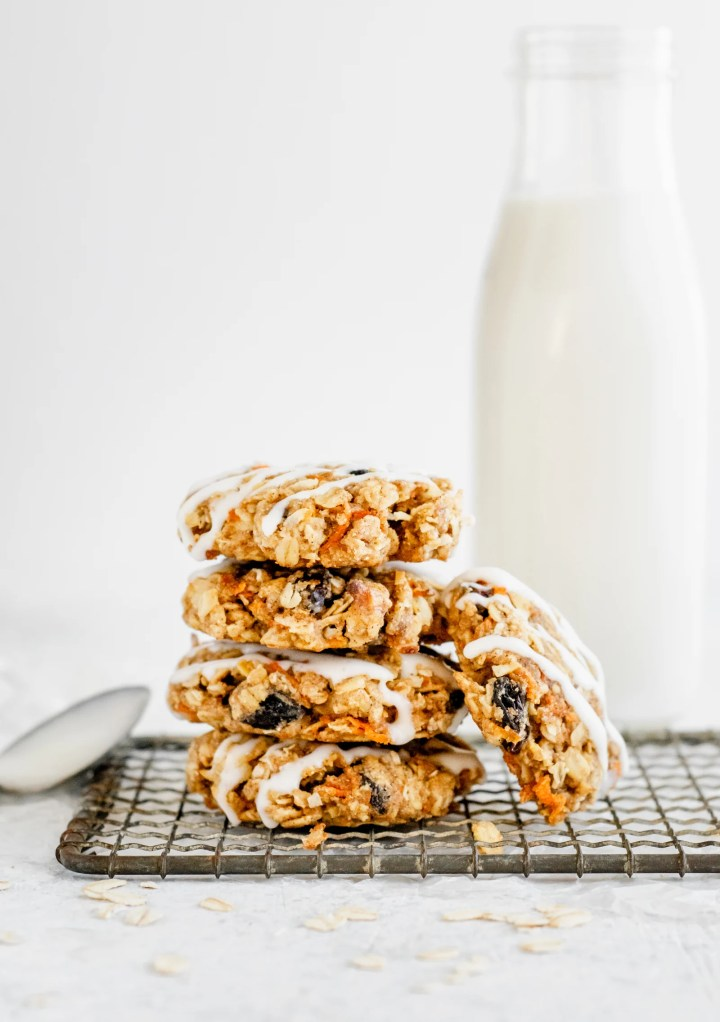 Carrot Cake Cookies Stacked On Top Of Each Other With A Milk Bottle In The Background