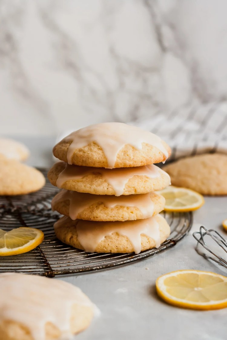 glazed lemon cookies in a stack on a wire rack next to lemon slices
