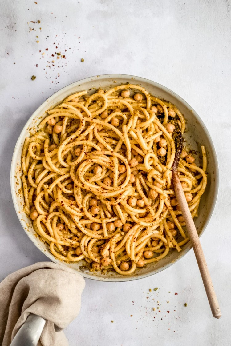 chickpeas and pasta in a skillet with a wooden spoon