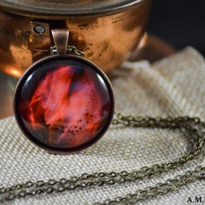A close-up of fire set in an Antique Copper bezel with a brass chain. Image captured in the late Summer of 2017 and pendant created in the Winter of 2019.